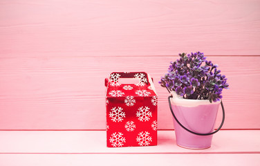 The ceramic pot with small plant put beside red gift box,on pink pastel wooden timber board