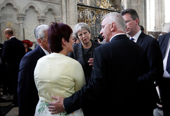 Britain's Prime Minister Theresa May speaks with relatives of soldiers who took part in the Battle of Amiens after a religious ceremony to mark the 100th anniversary of the World War I (WW1) battle