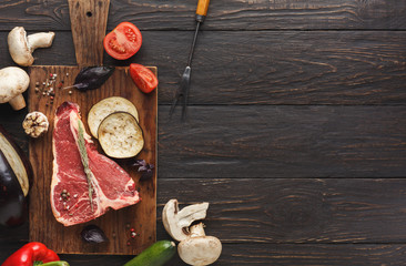 Raw t-bone steak with vegetables on wooden board