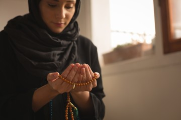 Muslim woman with prayer beads praying at home