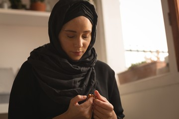Woman praying with prayer beads at home
