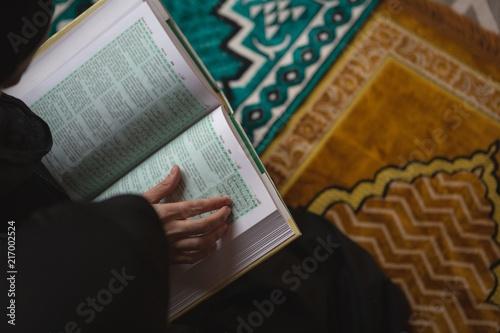 Muslim woman reading holy Quran
