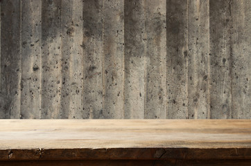 Empty table in front of exposed concrete textured wall background. For product display montage.