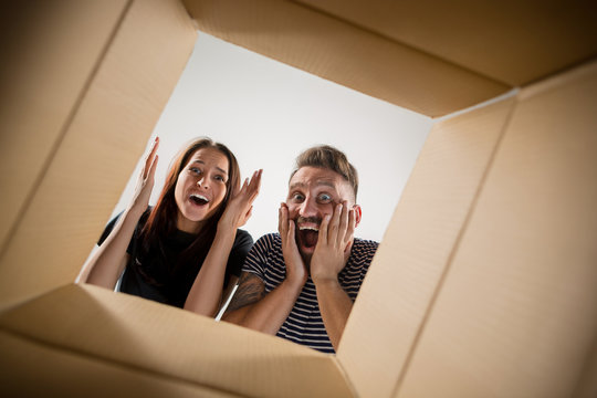 The surprised man and woman unpacking, opening carton box and looking inside. The package, delivery, surprise, gift lifestyle concept
