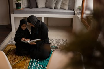 Muslim mother assisting her daughter to read holy Quran