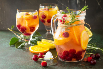 Homemade refreshing wine sangria or punch with fruits in glasses. Sangria cocktails with fresh fruits, berries and rosemary. On a stone or slate background, with a jug and ingredients. Copy space.