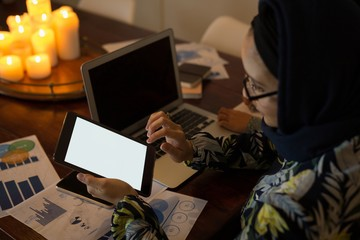 Muslim woman using digital tablet and laptop