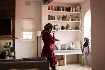 Muslim woman talking to her daughter while using phone