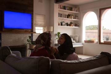 Muslim mother and daughter holding hands on sofa