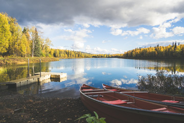 Pier and two red canoes on the Talkeetna lakes, open lake, autumn trees and reflection of clouds.