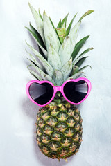 pineapple with sunglasses on rustic background.