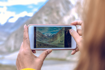 Woman using smart phone take a picture on beautiful Landscape of top Penzila valley in Karsha village, Zanskar, Ladakh, India.