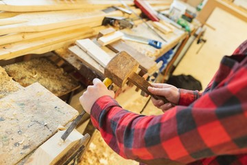 Male carpenter using chisel with hammer