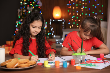 Little children drawing pictures at home. Christmas celebration