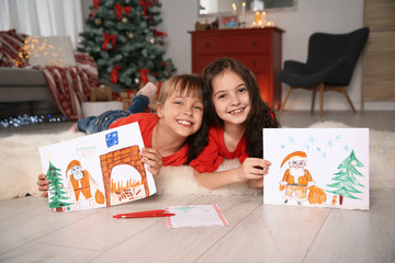 Little children with drawings and letter to Santa at home. Christmas celebration