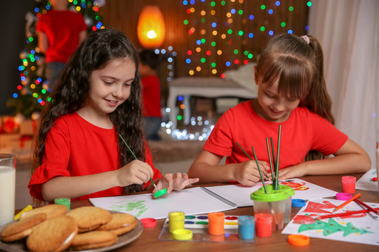 Little children painting pictures at home. Christmas celebration