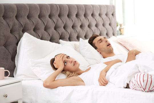 Young irritated woman lying on pillows in bed at home. Problem with snoring husband