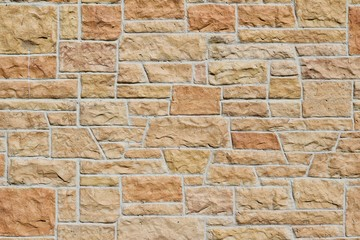 Aged fossiliferous limestone brick wall background in shades of orange, pink, yellow, and beige