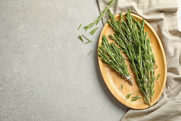 Wooden plate with fresh rosemary twigs on table, top view