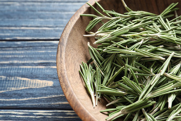 Plate with fresh rosemary twigs on wooden table, closeup