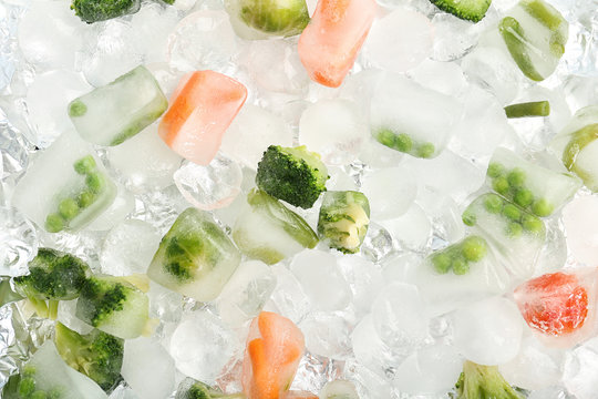 Frozen vegetables and ice cubes as background