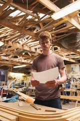 Male carpenter looking at chart in workshop