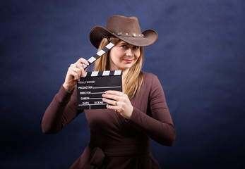 Young beautiful woman with clapperboard in cowboy hat. Movielover