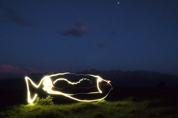 freezelight drawing by light of a LED flashlight in the air with mountains and sky in the background