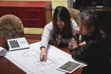 Couple discussing over blueprint