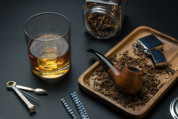 a smoking pipe and a chrome lighter in wooden tray, a pipe tamper tool, pipe cleaners, tobacco jar and a glass of whisky on the black table