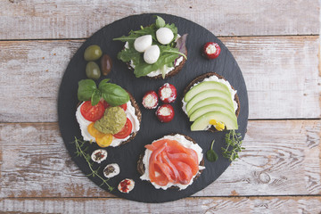 Variety of canape with salmon, avocado, mozzarella ,tomato,pesto,olives, cream cheese. Mix of different snacks and appetizers