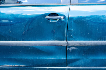 Crumpled doors against a blue car, scratches and dents