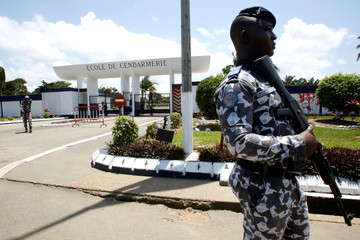 Ivorian gendarmes walk at the entrance of Abidjan's Ecole de Gendarmerie in which newly released Ivory Coast's former first lady Simone Gbagbo had been detained