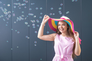 Cheerful young woman with colorful sun hat on gray background. Summer concept.