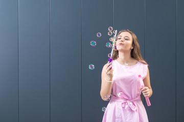 Teenage girl in beautiful dress blowing soap bubbles