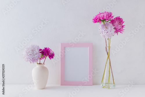 Mockup with a pink frame and pink flowers in a vase\