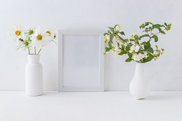 Mockup white frame and branches with green leaves in a vase