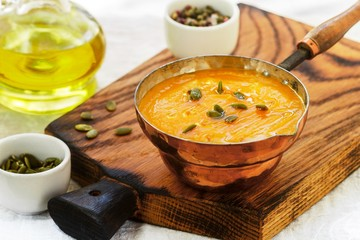 Pumpkin and carrot puree soup with seeds, pink pepper and olive oil. Tasty and healthy lunch for gourmets