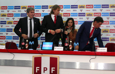 Peru's soccer coach Ricardo Gareca prepares for a photo with Nestor Bonillo, Romina Antoniazzi and Sergio Satin after news conference in Lima