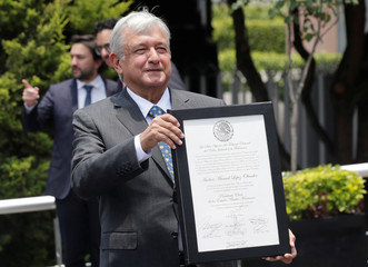 Mexican President-elect Andres Manuel Lopez Obrador shows the certificate that formally installs him as the country's next president, outside the headquarters of the electoral authority, in Mexico City