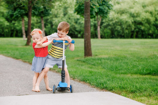 Two little Caucasian preschool children fighting hitting each other. Boy and girl can not share one scooter. Older sibling brother not giving his toy to younger sister. Communication problems.