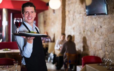 waiter with serving tray welcoming to restaurant