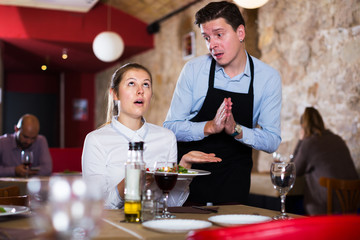 Dissatisfied woman talking with waiter