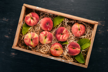 Flat peach in a wooden box. On a black wooden background. Top view. Free space for your text.