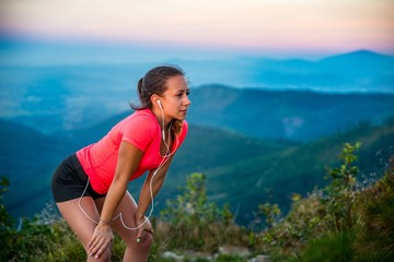 Young tired woman during trail running in mountains