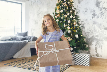 Adorable little girl with Christmas present by the Christmas tree