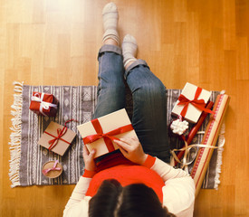 Young woman packing presents in Christmas time