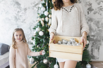 Woman holds a box with a lot of Christmas silver decorations near to the Christmas tree. Christmas holiday concept.