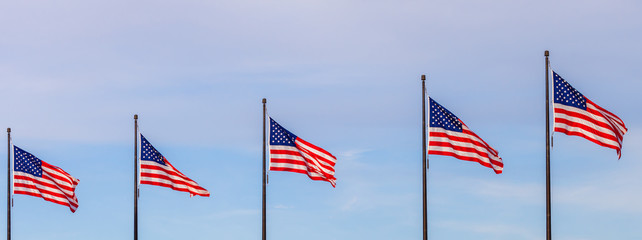 Waving flags of the United States on the Pier in Chicago with sky in the background
