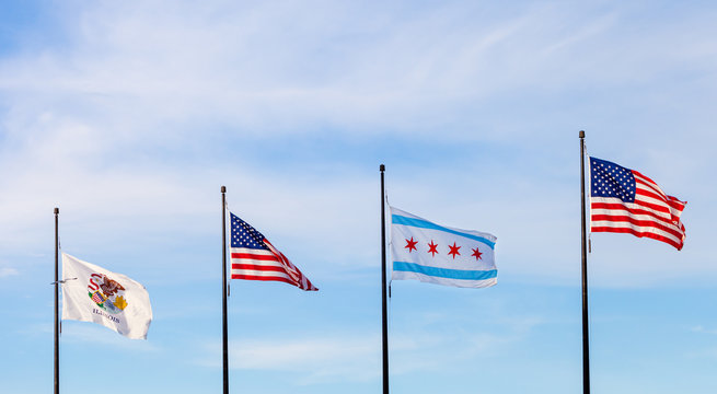 Waving flags of the state of Illinois, the United States and of the city of Chicago with sky in the background